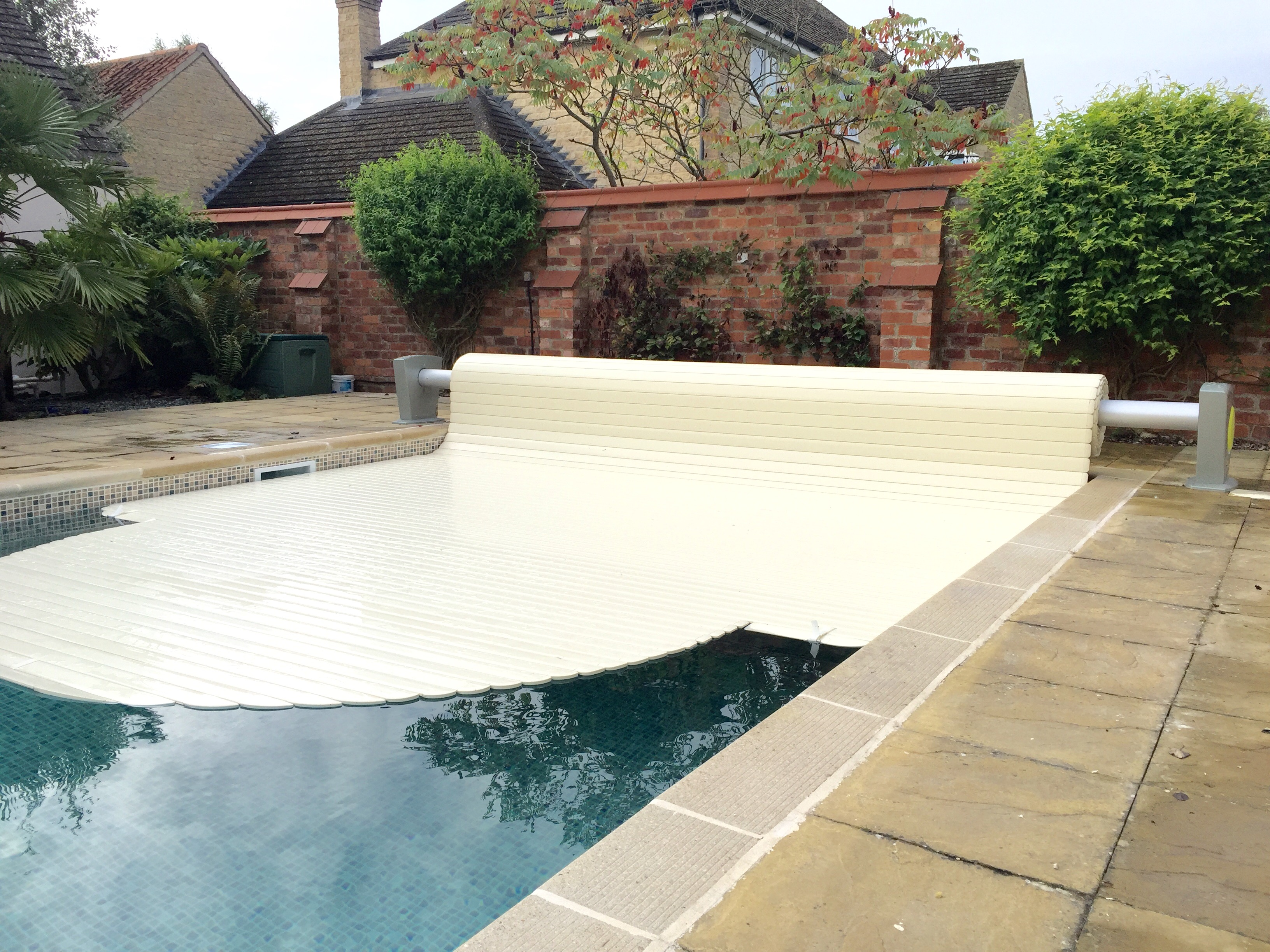 Slatted cover half on pool